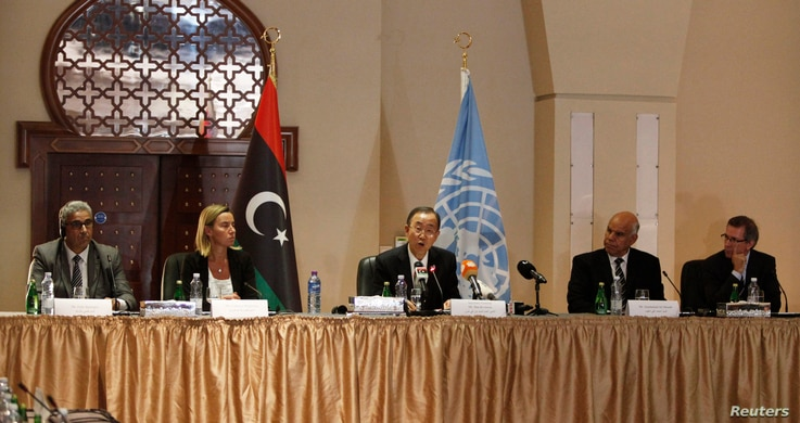 U.N. chief Ban Ki-moon, center, calls for peace during a meeting in Tripoli, Libya, on Oct. 11, 2014.