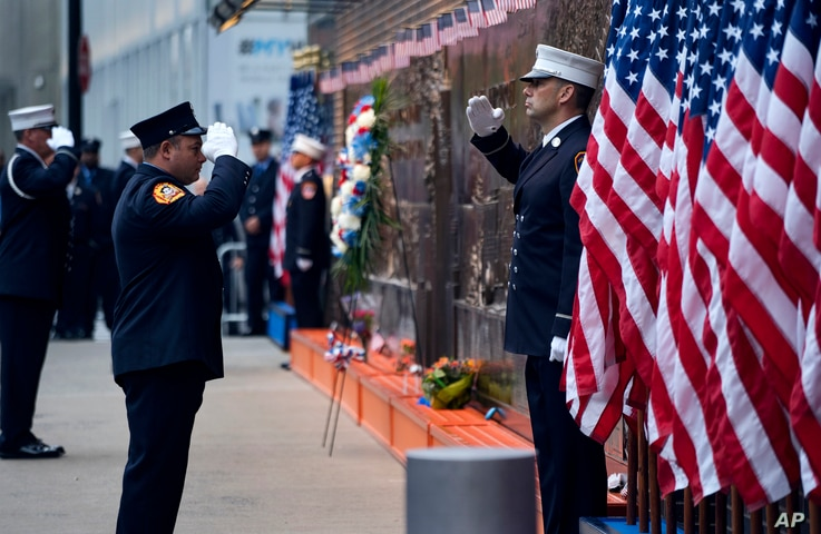 New York City firefighters salute in front of a memorial on the side of a firehouse adjacent to One World Trade Center and the 9/11 Memorial site during ceremonies on the anniversary of 9/11 terrorist attacks in New York, Sept. 11, 2018.