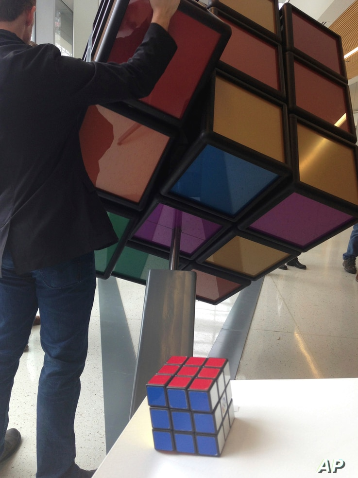 A traditional Rubik's Cube sits on a podium in the foreground while a person operates an oversized version shortly after its unveiling inside the University of Michigan's G.G. Brown engineering building in Ann Arbor, Mich., April 13, 2017.