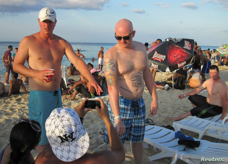 A tourist displays his tattoos on a beach on the outskirts of Havana, April 14, 2013.