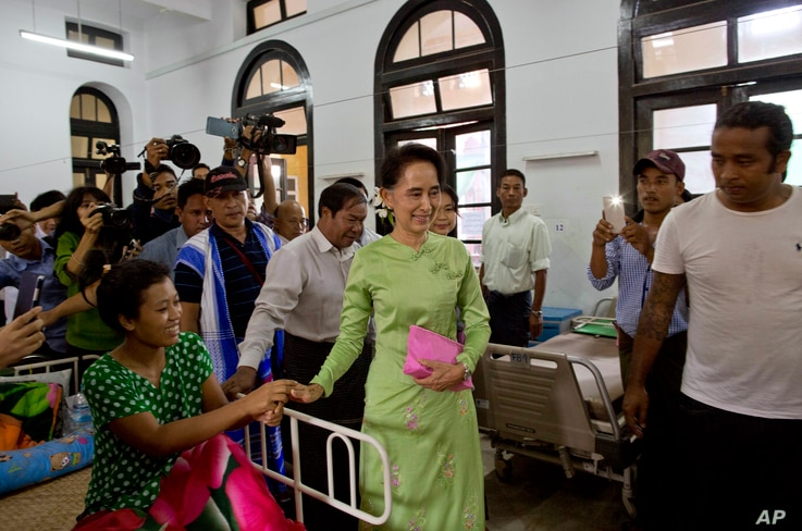 Myanmar's opposition leader Aung San Suu Kyi, center, greets a patient in a bed at Yangon General Hospital in Yangon, Myanmar, Oct. 30, 2015.
