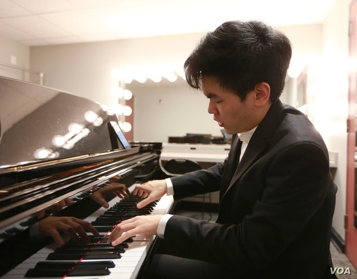 Daniel Hsu of the United States warms up in his dressing room before performing his Thursday evening recital in the Semifinal Round at the 15th Van Cliburn International Piano Competition.