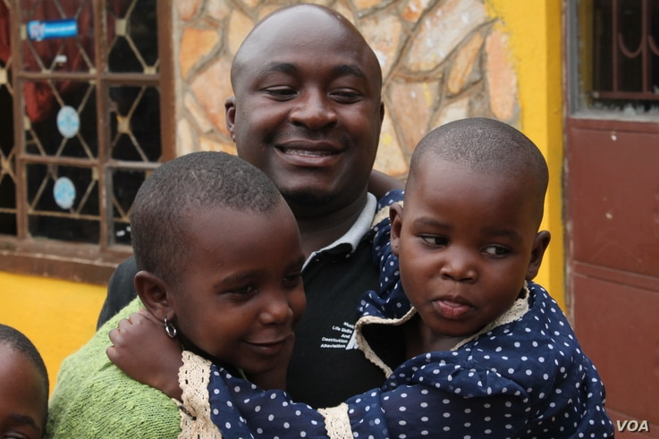 Bosco Segawa with two of the former street kids at his orphanage in Kampala, Uganda, Oct. 25, 2013. (Hilary Heuler for VOA)