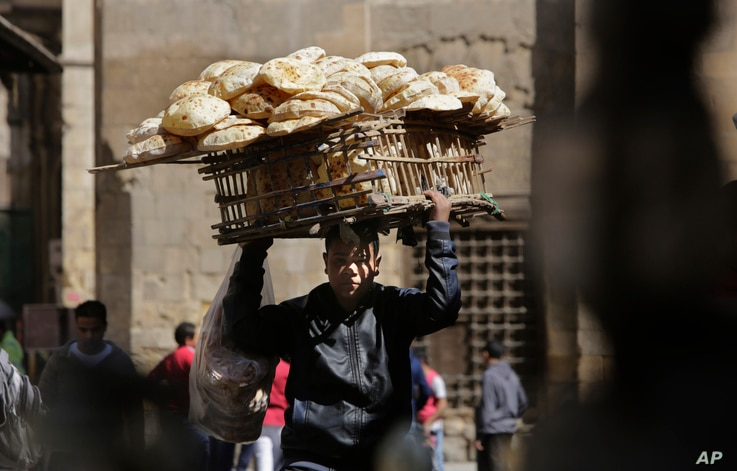 FILE - An Egyptian bread vendor looks for clients on el-Moez Street in historic Fatimid Cairo, March 12, 2015. In the privatization and investment drive of the 2000s, Egypt¹s economy achieved impressive economic growth, but it failed to translate in...