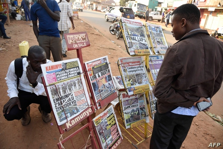 People gather around a newspaper stand to read the local daily papers on Feb. 17, 2016 ahead of tomorrow's presidential elections.