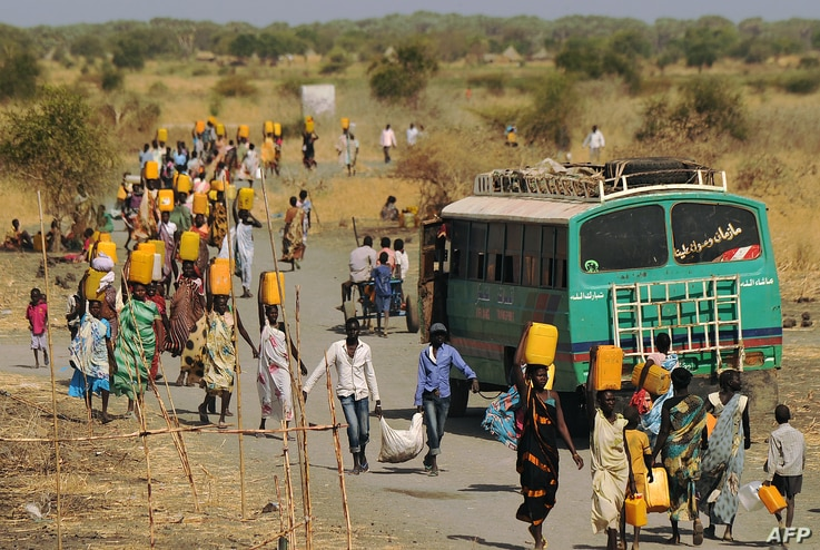 Internally displaced people carry water from outside as they walk toward the entrance of a United Nations Mission in the Republic of South Sudan base in Malakal, Feb. 6, 2014.
