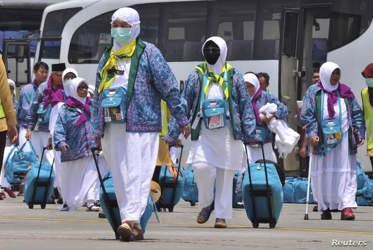 FILE - Indonesian Haj pilgrims walk towards their flight at the airport in Solo, Central Java province, Indonesia, Sept. 17, 2015, in this photo taken by Antara Foto.