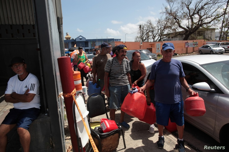 People queue at a gas station to fill up their fuel containers, after the island was hit by Hurricane Maria, in San Juan, Puerto Rico, Sept. 28, 2017.