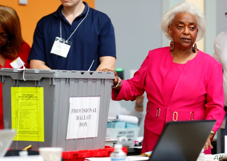 Broward County Supervisor of Elections Brenda Snipes, right, shows a ballot box that was found in a rental car after the elections and turned out to only contain election day supplies, as election employees sort ballots and prepare to count them, Mon...