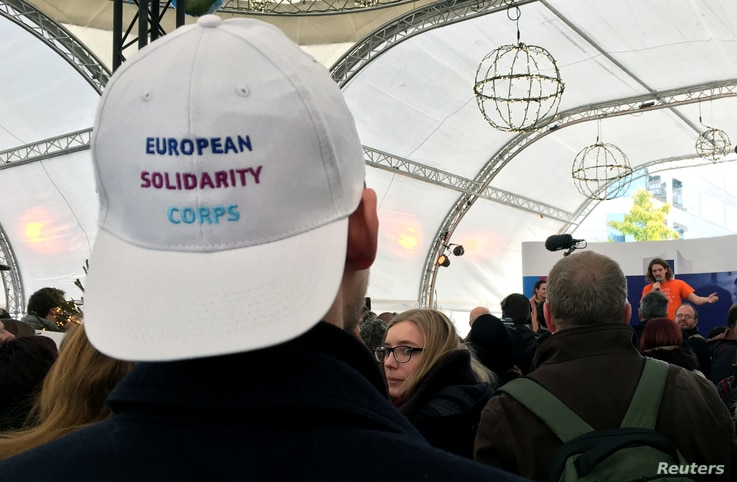 The European Solidarity Corps, a new initiative for young people to travel and help out people in difficulty across the continent, offered baseball caps to prospective enrollees outside the European Commission headquarters in Brussels, Belgium, Dec. ...