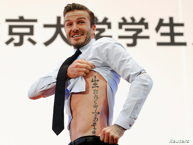"Beckham shows his tattoo after he was asked to by students at Peking University during his visit to Beijing March 24, 2013. The tattoo in Chinese characters reads, ""Life and death are determined by fate, rank and riches decreed by Heaven."""