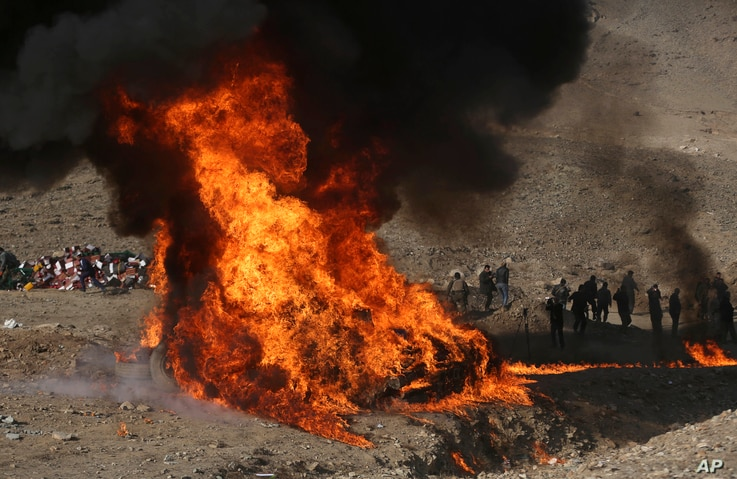 FILE - Afghan security personnel watch as flames and smoke rise after opium and narcotics are burned in a ceremony in Kabul, Afghanistan, Dec. 20, 2016.