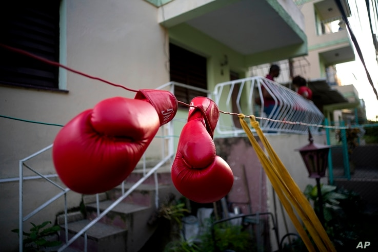 Idamelys Moreno's boxing gloves hang on a line to dry, after a training session in Havana, Cuba, Jan. 19, 2017.