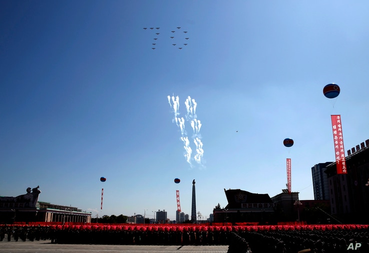 Airplanes forming the number 70 fly in formation and fire flares during a parade for the 70th anniversary of North Korea's founding day in Pyongyang, North Korea, Sept. 9, 2018.