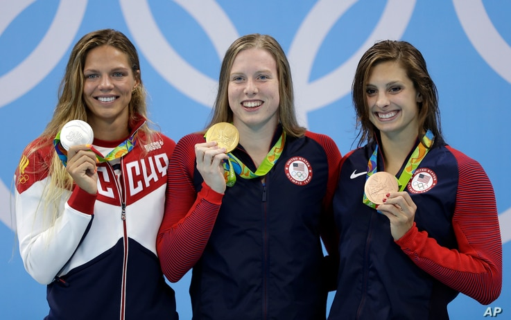 United States' gold medal winner Lilly King is flanked by Russia's silver medal winner Yulia Efimova, left, and United States' bronze medal winner Katie Meili during the ceremony for the women's 100-meter breaststroke final during the swimming compet...