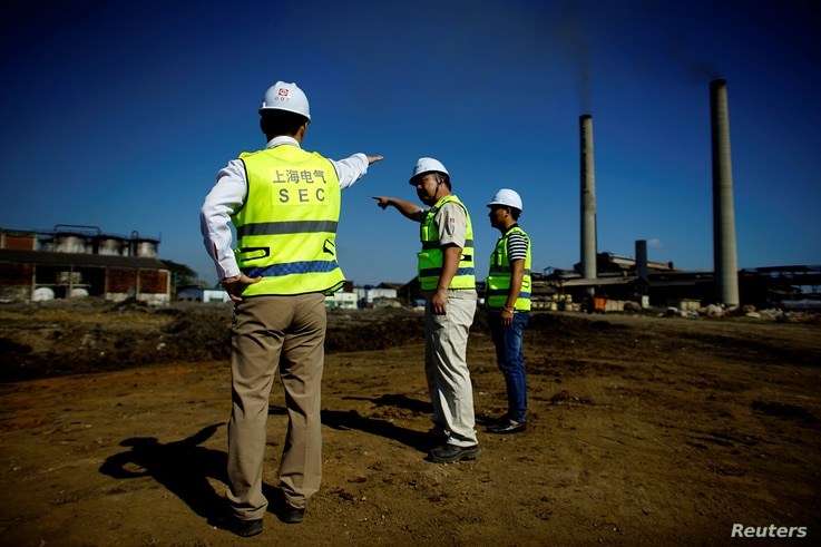 Chinese employees of Shanghai Electric company supervise the construction site of a biomass power station in Ciro Redondo, Cuba, Feb. 9, 2017.