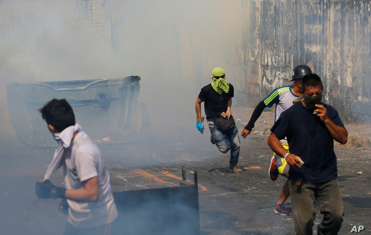 Demonstrators run away from a cloud of tear gas during clashes with the Bolivar National Guard in Urena, Venezuela, near the border with Colombia, Feb. 23, 2019.