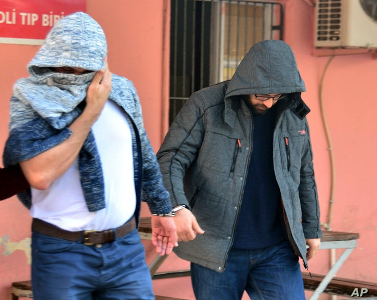 Two men, identified by Turkey's state-run news agency, as Mahamad Laban, 45, right, and Mohammed Tofik Saleh, 38, walk to a police van outside a police station in Adana, Turkey, Feb. 11, 2017. The Anadolu news agency said that the arrested men were s...