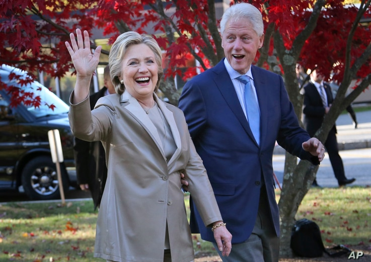 FILE - Then-Democratic presidential candidate Hillary Clinton, and her husband former President Bill Clinton, greet supporters after voting in Chappaqua, N.Y., Nov. 8, 2016.