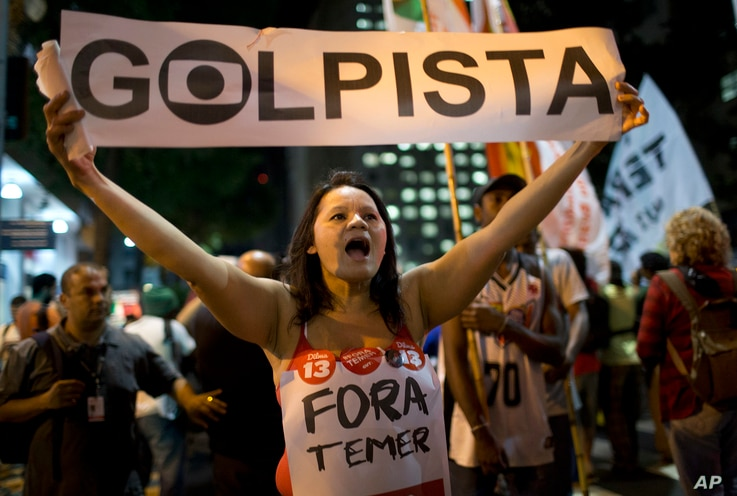 """A demonstrator holds a sign that reads in Portuguese """"Coup leader """" during a march against acting President Michel Temer and in support of Brazil's suspended President Dilma Rousseff in Rio de Janeiro, Brazil, Aug. 29, 2016."""