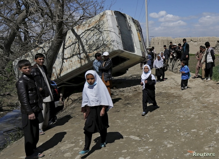 Schoolgirls walk past a damaged mini-bus after it was hit by a bomb blast in the Bagrami district of Kabul, Afghanistan April 11, 2016.
