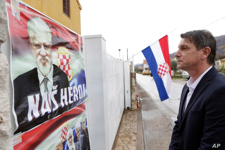 """Bosnian Croat Pero Pervisic, 49, a friend of the late Slobodan Praljak, pays his respects in front of house where Praljak was born, in  Capljina, Bosnia, Nov. 30, 2017. On the house are posters reading, """"Our hero."""""""