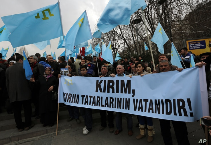 """Turks of Crimean Tatar origin waves  Crimean flags and hold a banner that reads """" Crimea is the homeland of Crimean Tatars """" as they demonstrate to protest against Russia's military intervention in Crimea, Ukraine, in Ankara, Turkey, Sunday, March 2,..."""