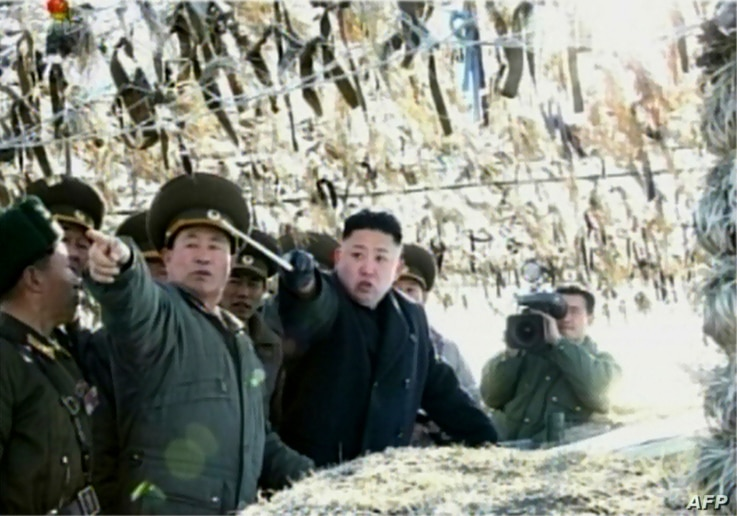 Screen grab shows North Korean leader Kim Jong-Un (C) pointing to a South Korean island during a trip to an artillery unit on Wolnae Island near the disputed maritime frontier with South Korea, Mar. 12, 2012.