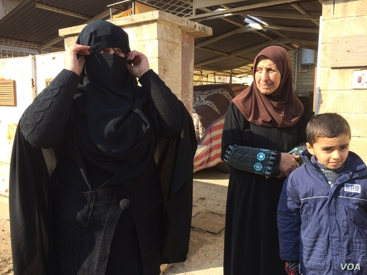 Dalia covers herself with her veil to show journalists what she looked like under IS rule. When authorities were on the streets, she says, she also had her eyes covered with another layer of fabric in Mosul, Iraq, Jan. 23, 2017. (H. Murdock/VOA)