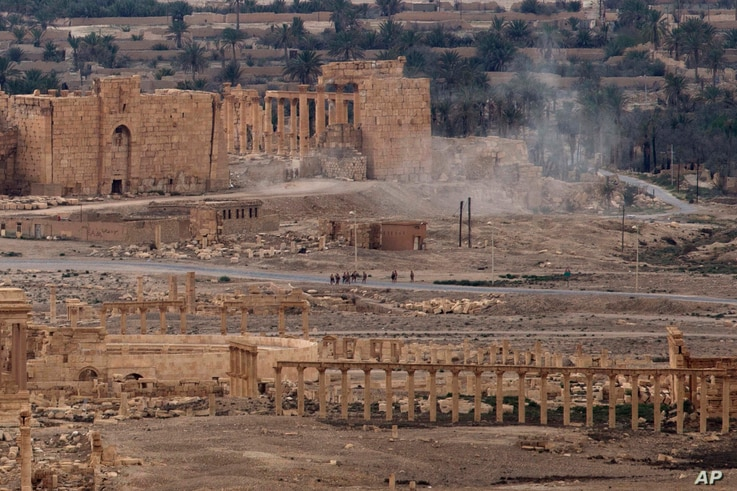 FILE - In this, April 14, 2016 file photo, Russian soldiers stand on a road as smoke rises from a controlled land mine detonation by Russian experts inside the ancient town of Palmyra, Syria. An American heritage organization says the Russian milita...