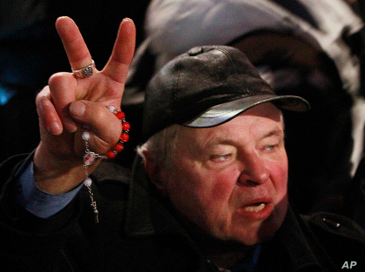 A supporter of  the government holds a rosary and shows a victory sign during the demonstration organized by the ruling Polish party Law and Justice in Warsaw, Poland, Tuesday, Dec. 13, 2016.