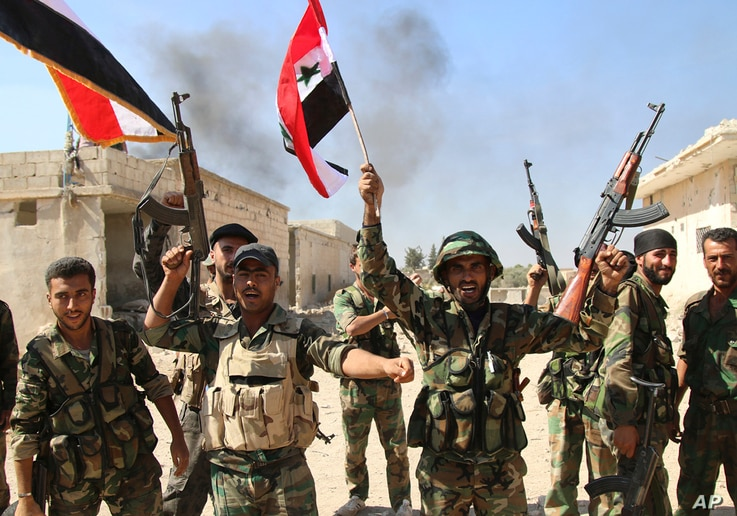 In this photo taken on Oct. 11, 2015, Syrian soldiers waving Syrian flags celebrate the ?apture of Achan, Hama province, Syria.