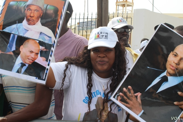 A young woman holds up pictures of Abdoulaye Wade and his son Karim as she waits for the former President at Dakar international airport, Dakar, Senegal, July 10, 2017. (S. Christensen/VOA)