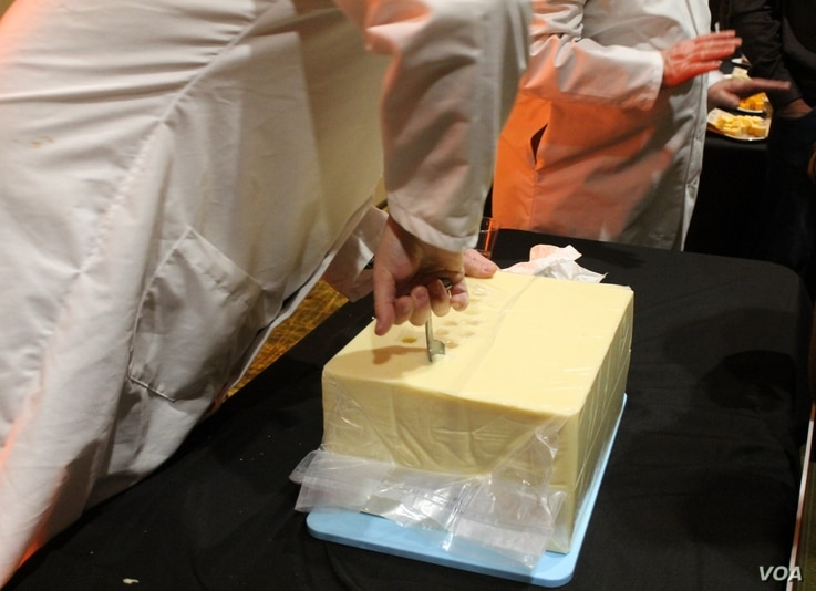 Judges at the U.S. Cheese Championship give visitors to the gala a chance to see how they do their job and to ask questions, in Green Bay, Wis., March 7, 2019. The first step is pulling out a piece of cheese to sample from a 40-pound block of Cheddar...