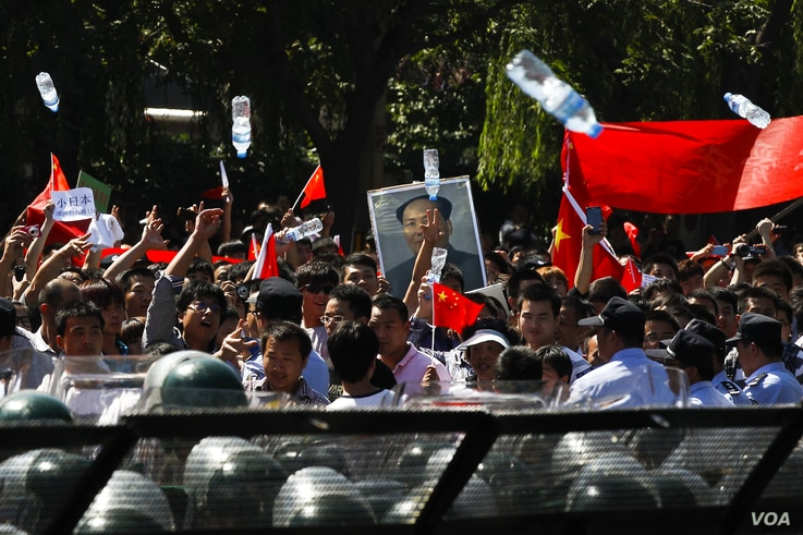 Anti-Japan protesters throw water bottles towards the Japanese Embassy while marching on a street outside the embassy, Beijing, China, September 18, 2012.