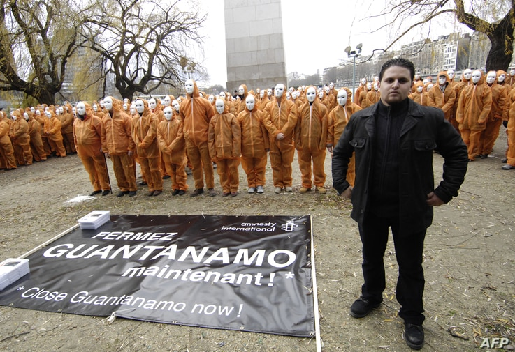 Amnesty International activists dressed in orange as the Guantanamo Bay prisonners, pose with French former prisonner, Mourad Benchellali, in front of a replica of the U.S. Statue of Liberty, in Paris, Jan. 6, 2007..