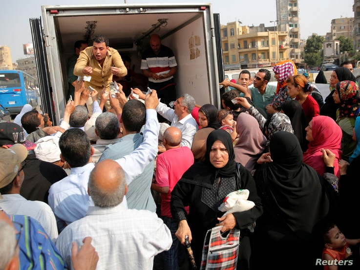 Locals gather to buy subsidized sugar from a government truck after a sugar shortage in retail stores across the country in Cairo, Egypt, October 14, 2016. Picture taken October 14, 2016.