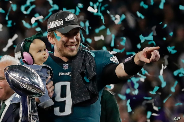 Philadelphia Eagles quarterback Nick Foles (9) holds his daughter, Lily James, after winning the NFL Super Bowl 52 football game against the New England Patriots, Sunday, Feb. 4, 2018, in Minneapolis. The Eagles won 41-33.