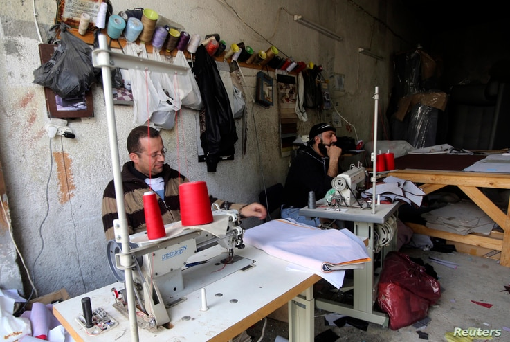 FILE - Palestinian workers sit during a power cut by Israel's electric company at a local company in the West Bank city of Nablus, Feb. 25, 2015.