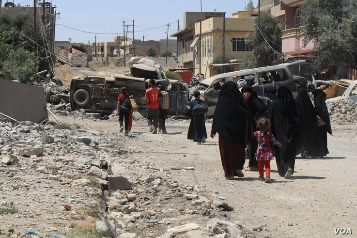 Most families running arrive exhausted from violence, hunger and heat and still wearing IS-mandated clothing, in Mosul, Iraq, June 4, 2017. (H. Murdock/VOA)