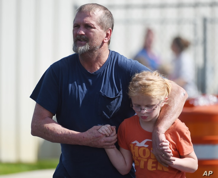 Joey Taylor walks with his daughter, Josie, after picking her up at Oakdale Baptist Church in Townville, S.C., Sept. 28, 2016. Students were evacuated to the church after a shooting at Townville Elementary School.