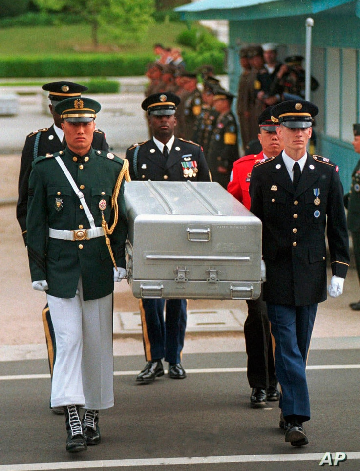 FILE -  U.N. honor guards carry a coffin containing the remains of an American soldier after they were returned by North Korea, at the border village of Panmunjom, South Korea, May 14, 1999.