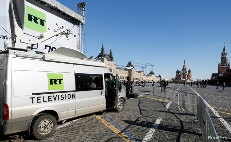 FILE - Vehicles of Russian state-controlled broadcaster Russia Today (RT) are seen at Red Square in central Moscow, March 18, 2018.