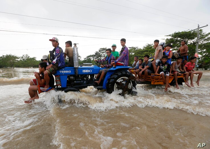 Commuters ride a farm tractor as it maneuvers through strong floodwaters along a highway in La Paz township, Tarlac province in northern Philippines, October 20, 2015.