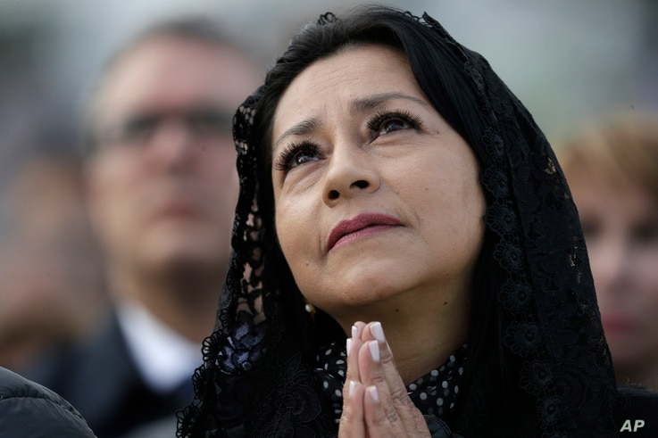 A woman prays as Pope Francis celebrates Mass at the Simon Bolivar Park in Bogota, Colombia, Sept. 7, 2017.