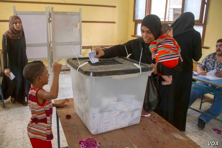 A woman casts her ballot at a polling station in the neighborhood of Bashteel in Giza, Egypt, in the 2014 elections.
