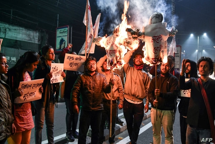 Student activists burn effigies of India's Prime Minister and Chief Minister of Assam in Guwahati, India, on Jan, 8, 2019, after India's lower house passed legislation that will grant citizenship to members of certain religious minorities but not Mus...