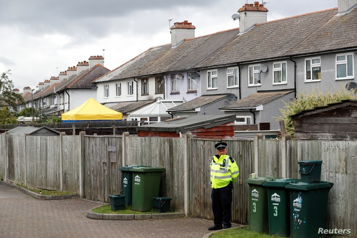 A police officer stands on duty at the back of a property being searched after a man was arrested in connection with an explosion on a London Underground train, in Sunbury-on-Thames, Britain, Sept. 17, 2017.