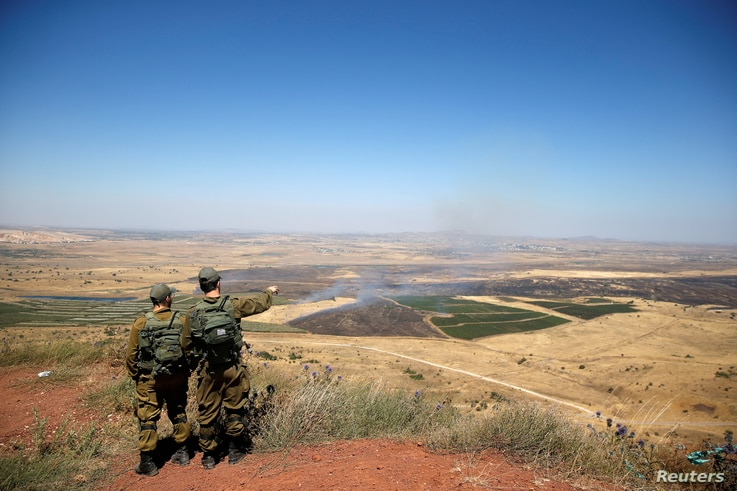 FILE - Israeli soldiers look at the Syrian side of the Israel-Syria border on the Israeli-occupied Golan Heights, Israel, July 7, 2018.