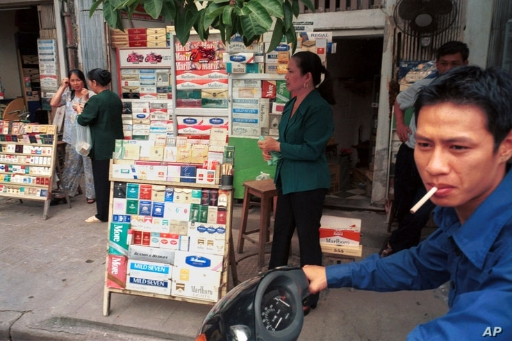 FILE - A young motorcyclist stops to buy a pack of cigarettes from a street-side vendor in Hanoi, May 12, 1999.